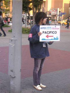 桜木町駅前でAPECの案内板を持つ女性